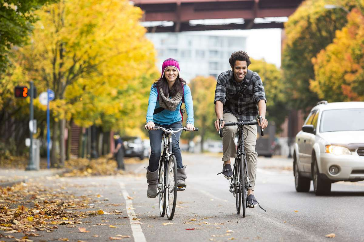 A man and woman ride along a bike lane with golden fall colors in the trees behind them.