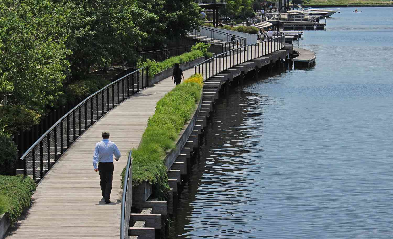 Vista trasera del hombre caminando sobre la pasarela sobre el río Milwaukee