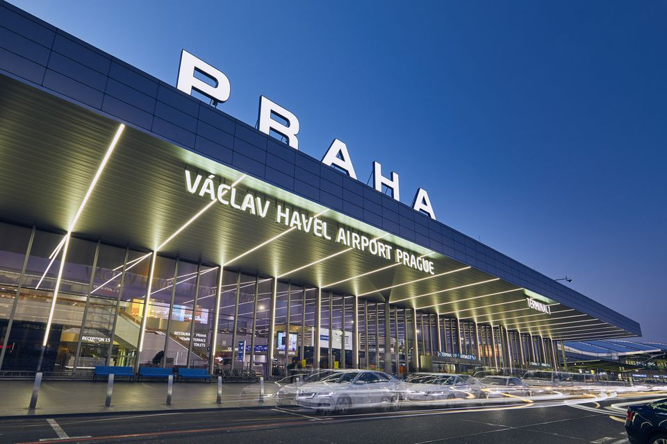 "Exterior of Vaclav Havel Airport Prague at twilight. There is a large sign that says ""Praha"" on top of a large overhang. Under the overhang there is a sign that says ""Václav Havel Airport Prague."" The signs are iluminated. There is a long exposure shot of a silver car driving on the road in front of the airport entrance"