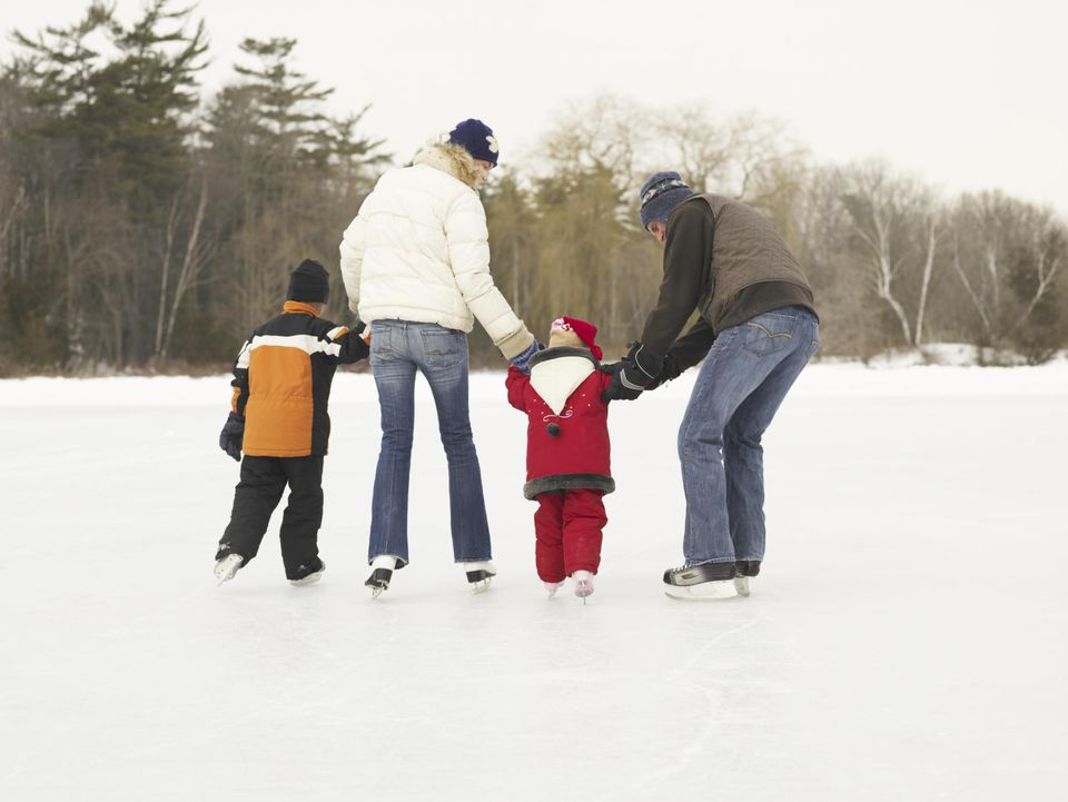 Family skating on frozen lake, rear view