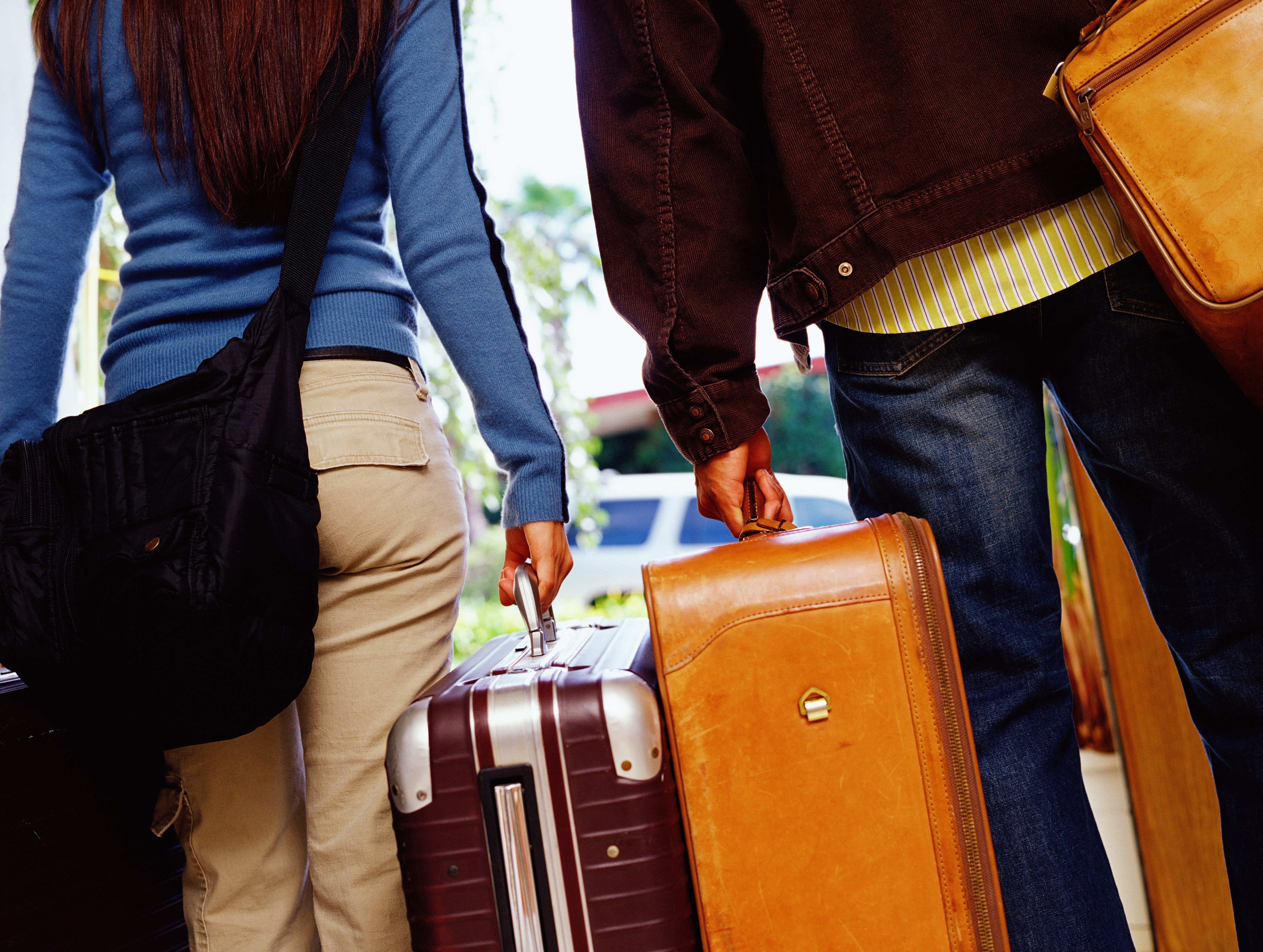 Young couple carrying luggage, low section, rear view