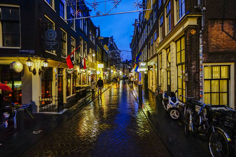 A rainy street in Amsterdam at dusk.