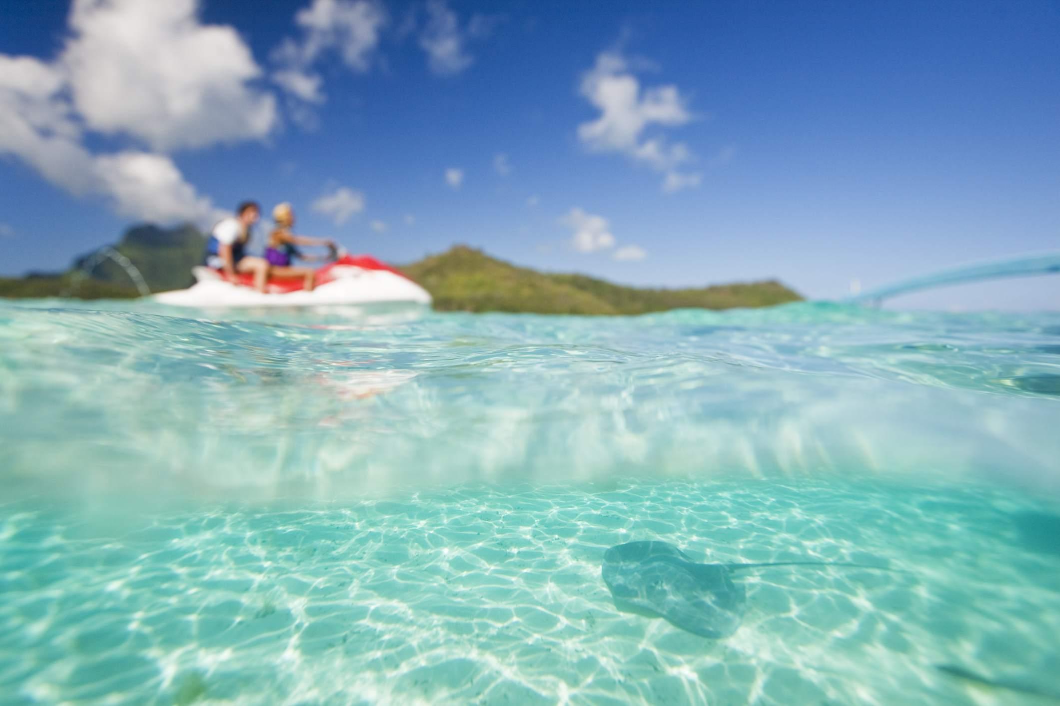 Waterscooter passing by stingray swimming on floor of Bora Bora Lagoon.