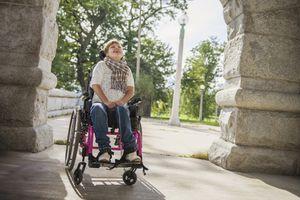 Paraplegic woman in wheelchair under stone arch