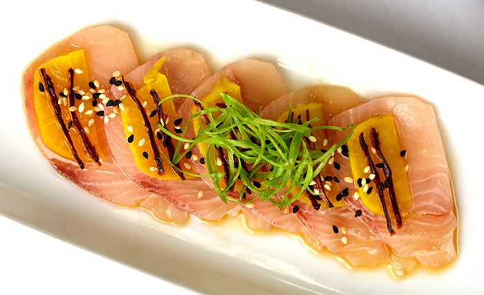 Hamachi crudo with julienned scallions, sesame seeds, pickled daikon, sun-dried tomato vinaigrette and serrano