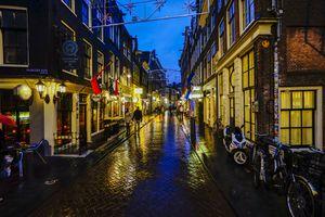 A rainy street in Amsterdam at dusk.