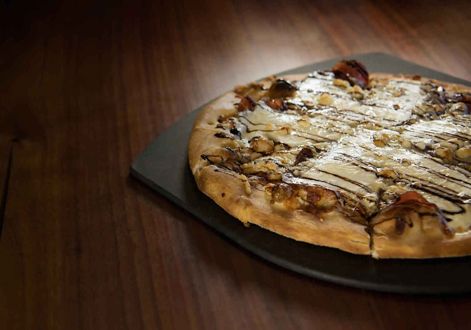 white pizza on a black pizza board on a dark wood table
