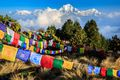 Tibetan prayer flags hanging on top of Poon Hill in Annapurna Conservation Area, Gandaki, north-central Nepal, with the majestic peak of Dhaulagiri in the background