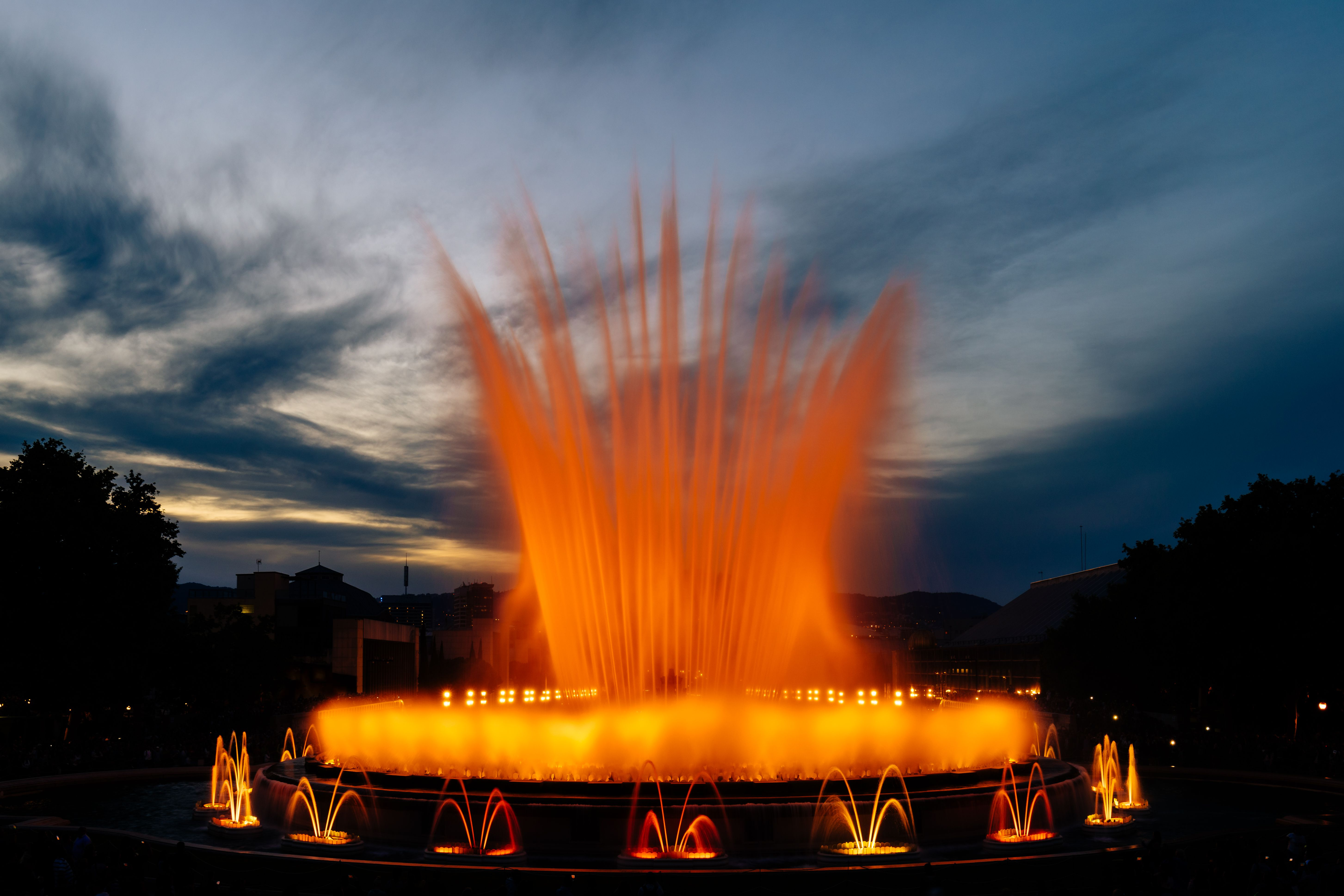 A fountain show with red lights lighting up the night sky