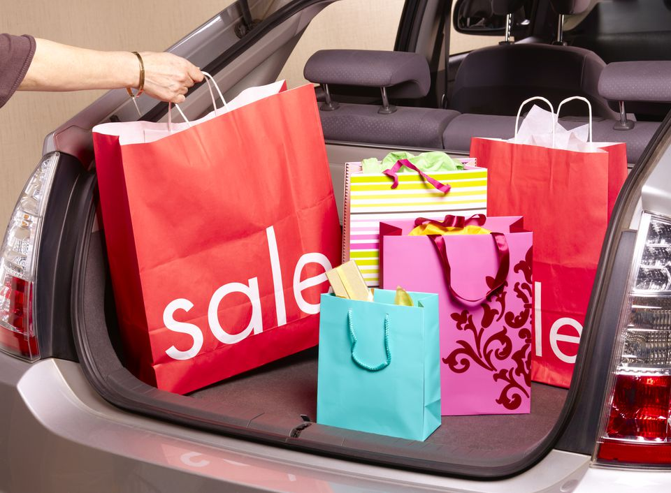 5265a2710e8 Woman putting sale carrier bag in car boot. Peter Dazeley / Getty Images.  UK outlets for discount ...