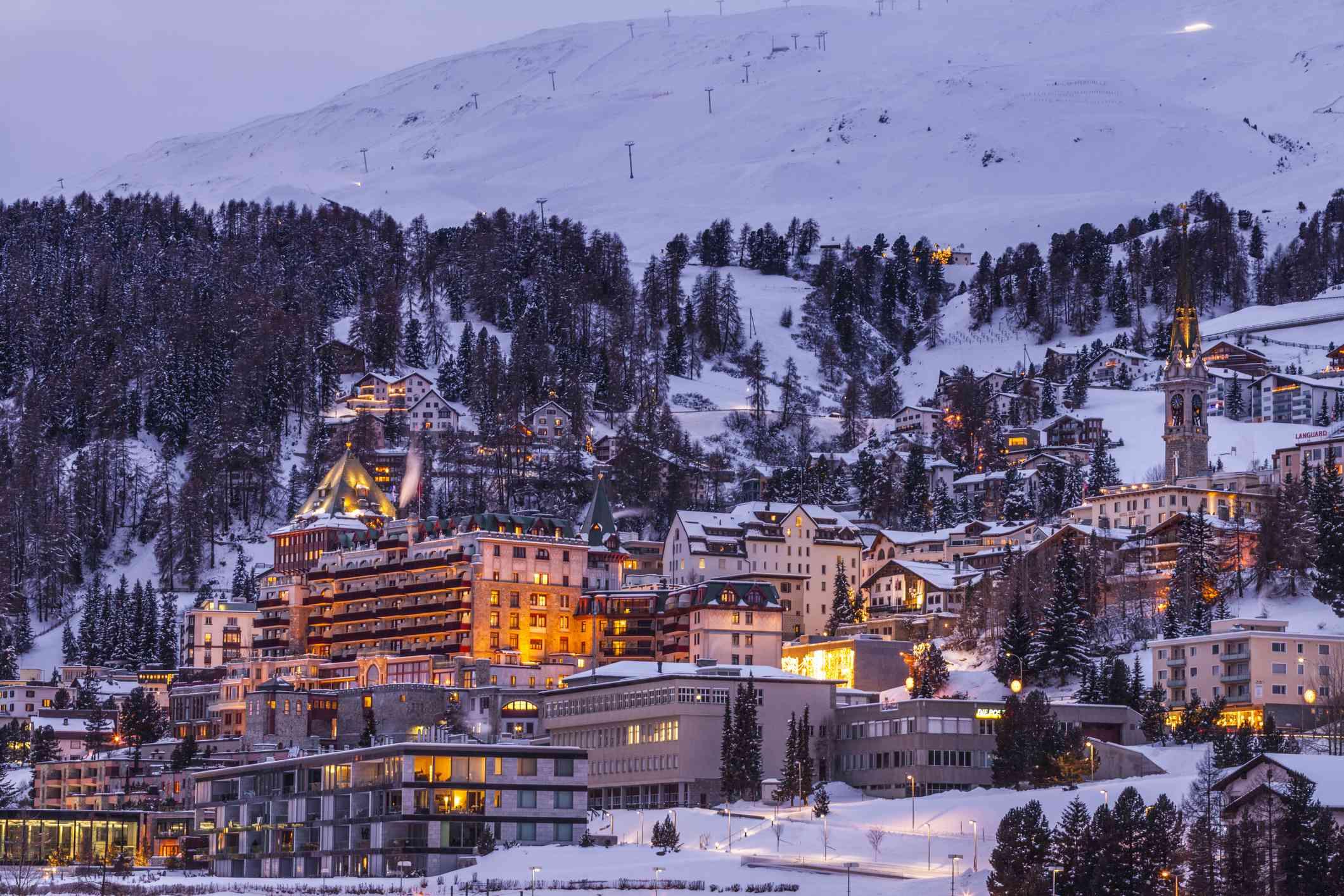 Village beneath mountain on snow covered landscape illuminated in the evening, Sankt Moritz, Switzerland