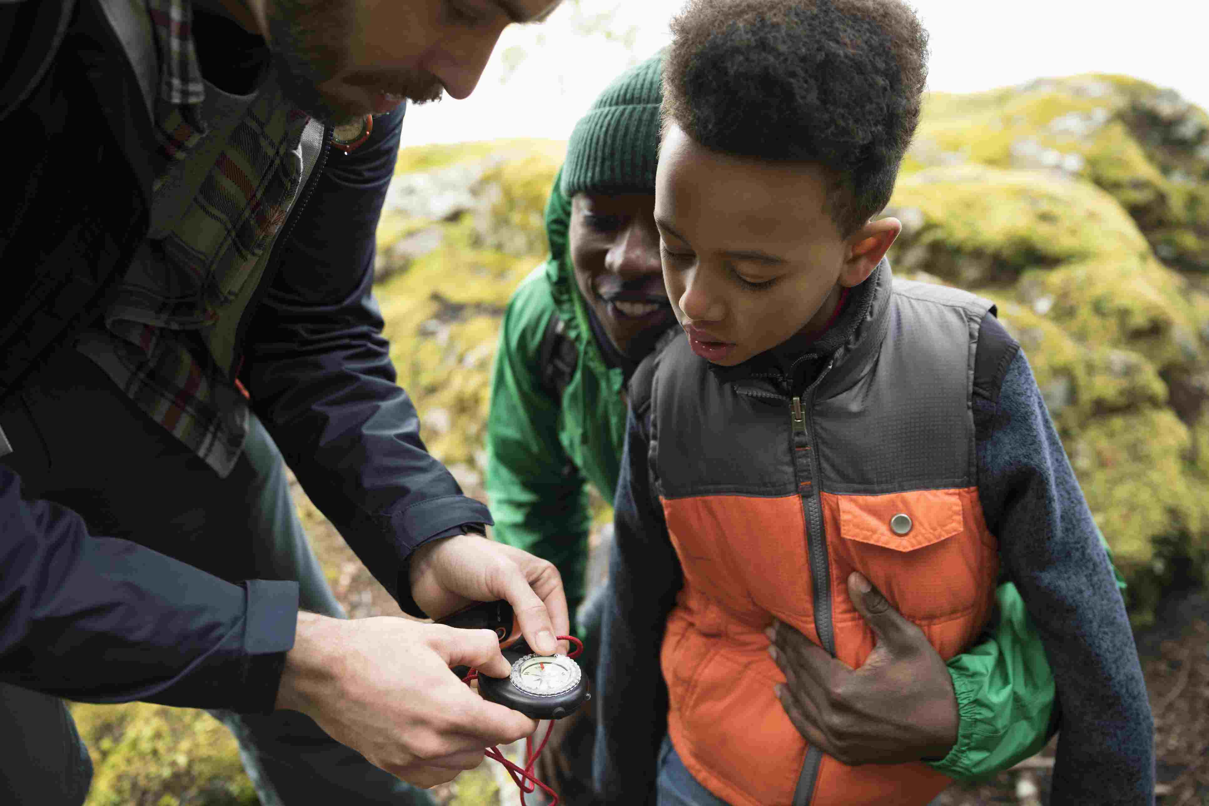 Curious boy hiker looking at compass