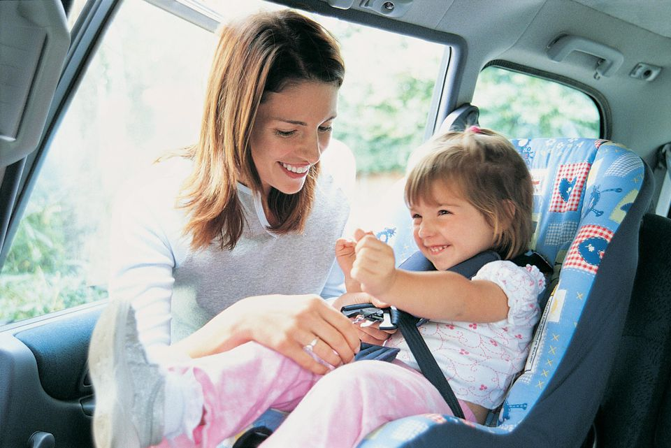 Mother Checking Her Toddlers Child Seat In A Car