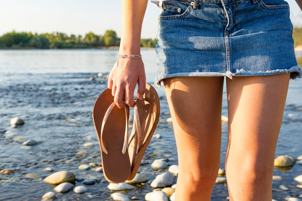 Woman Holding Flip-Flop at Beach