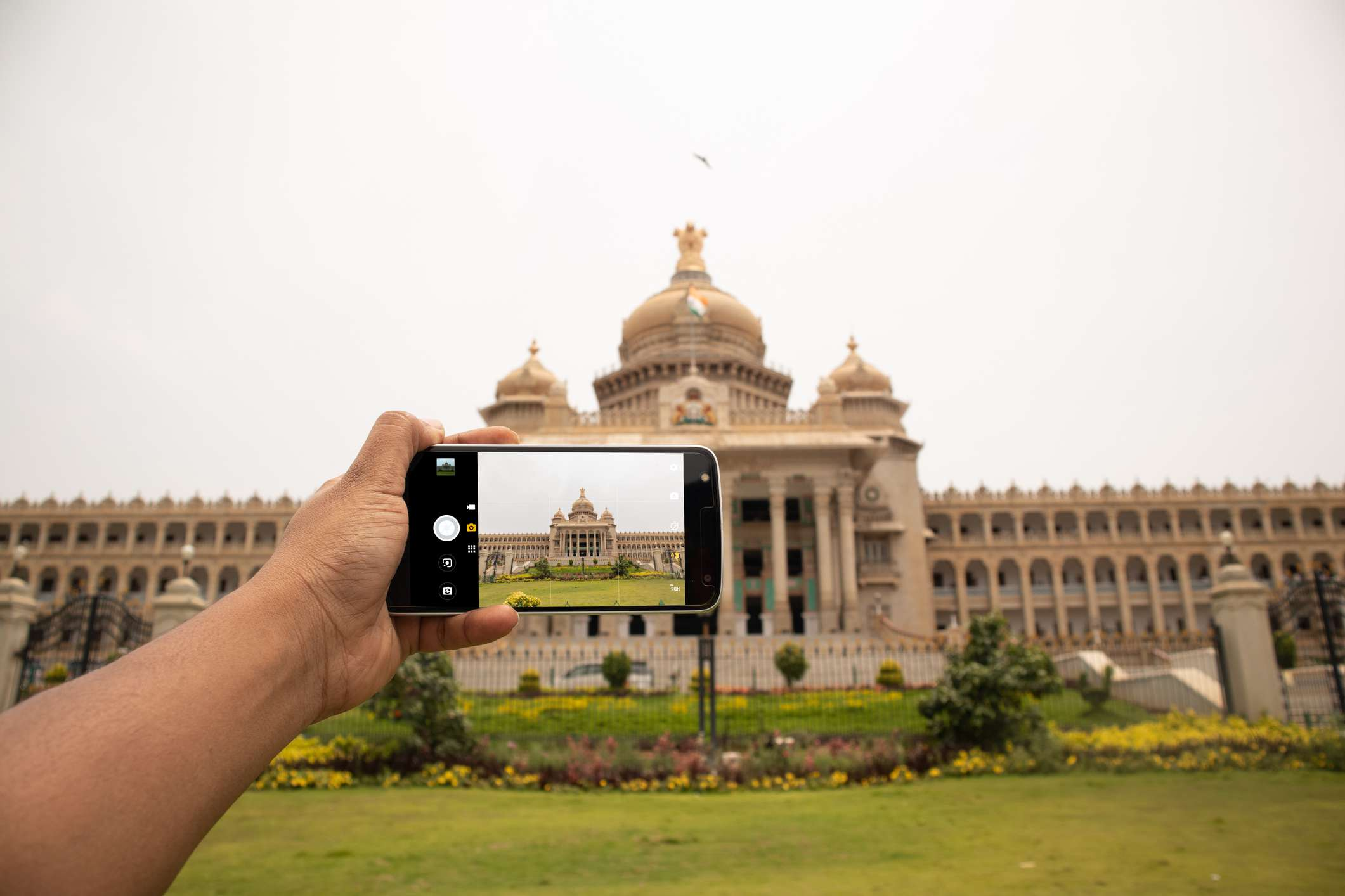 Hands showing of taking a picture of Vidhana soudha