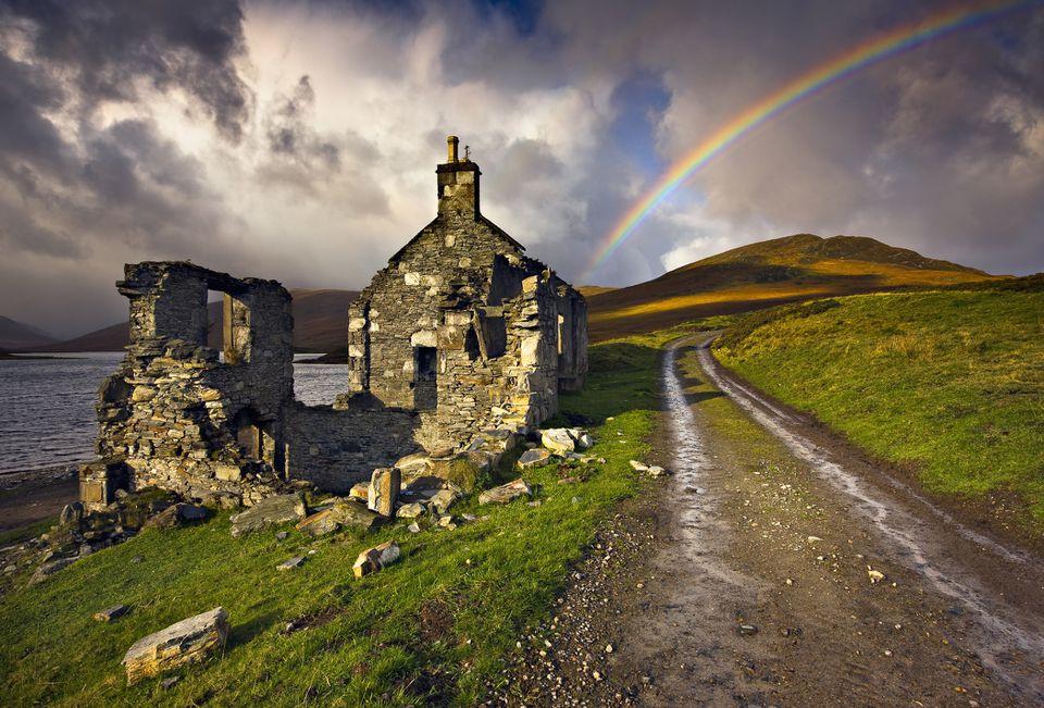 Casa abandonada por un lago remoto, cielos dramáticos y arcoiris