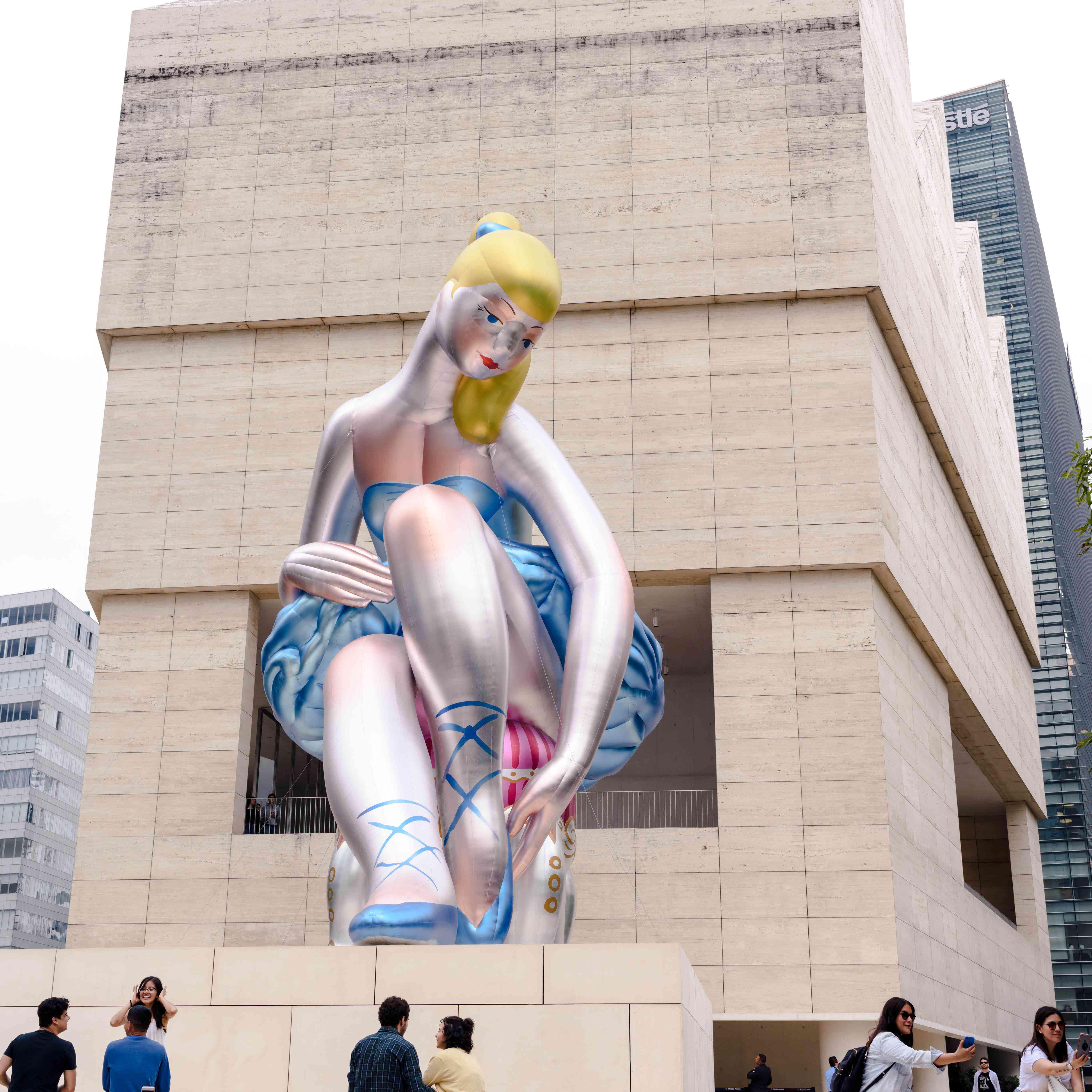 The exterior of Jumex museum with a large statue of a ballerina