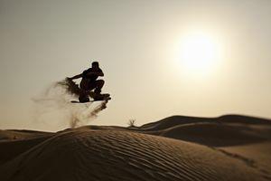man sandboarding in the desert