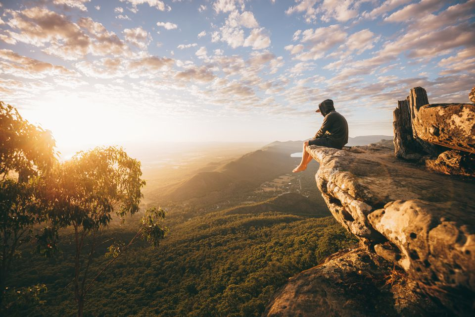 person sitting over a cliff ledge and looking at the views while hiking