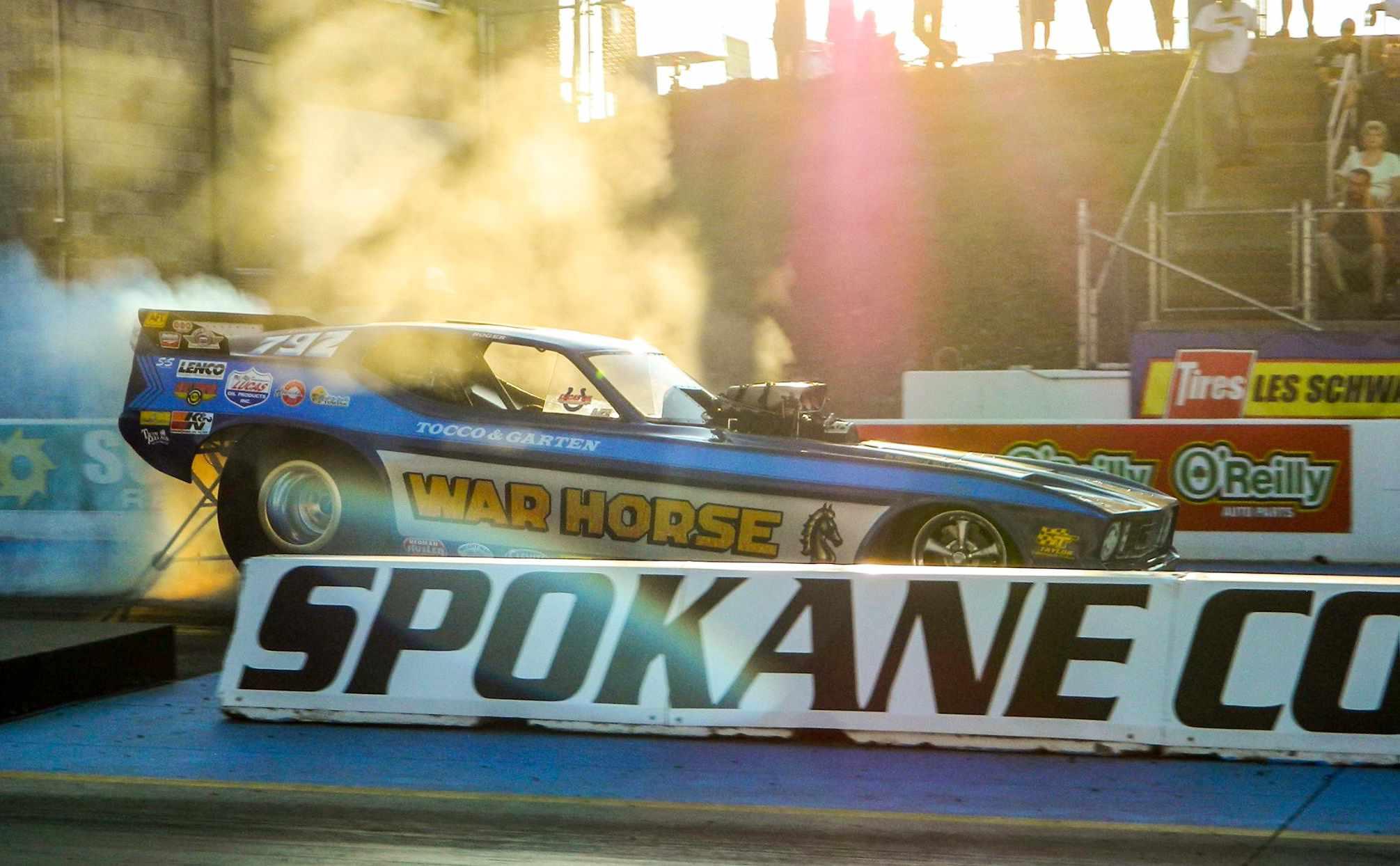 Un auto de carrera girando neumáticos y levantando polvo en la pista de rodadura