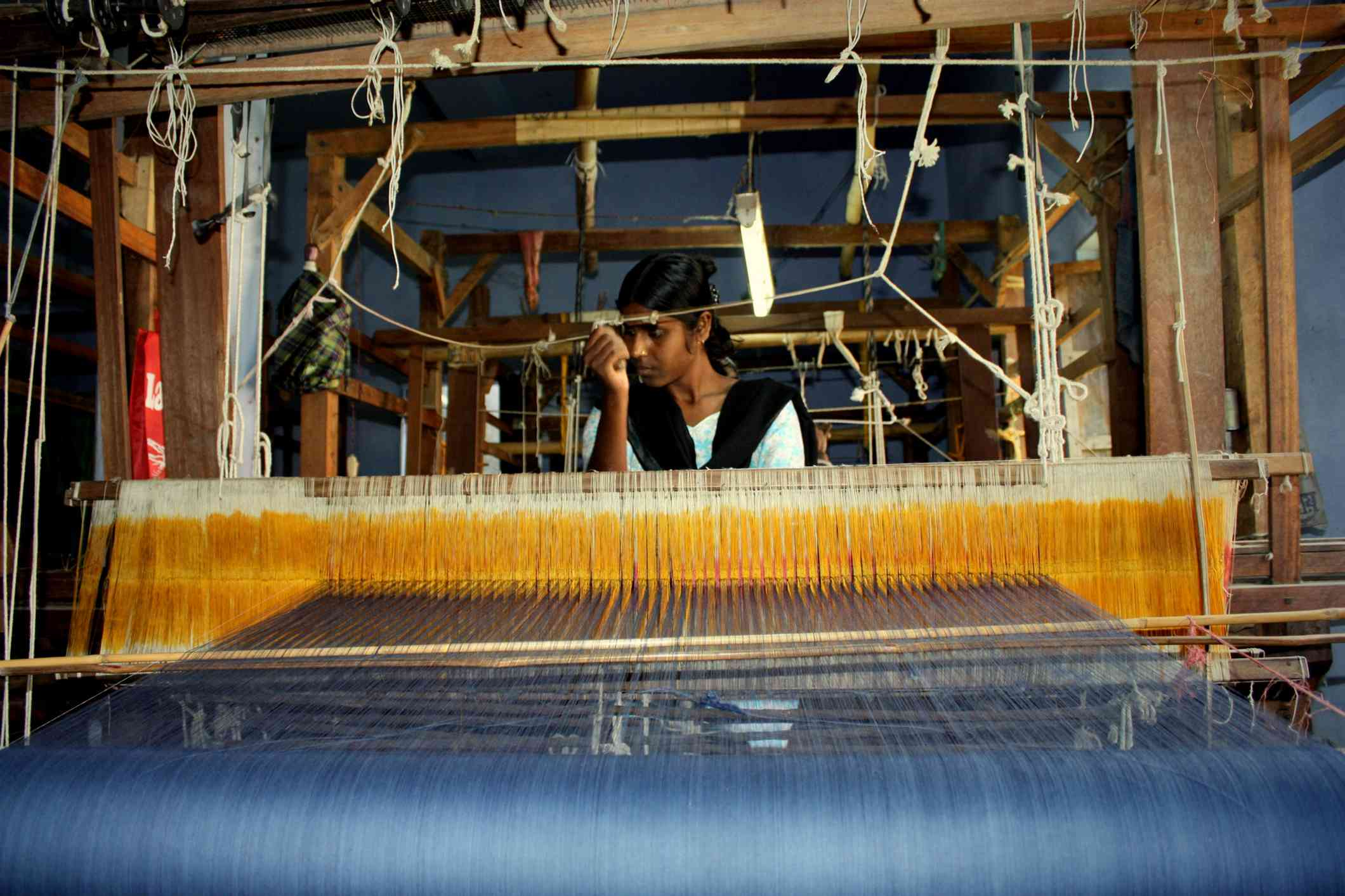 Young Indian woman sitting at a loom weaving fabric for a sari