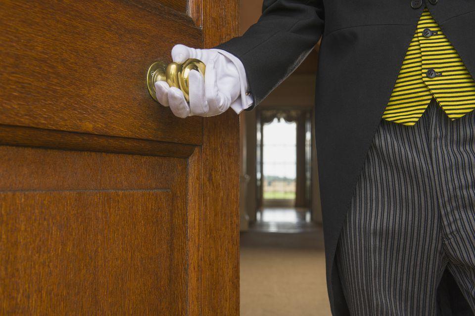 Close up of Caucasian butler opening door