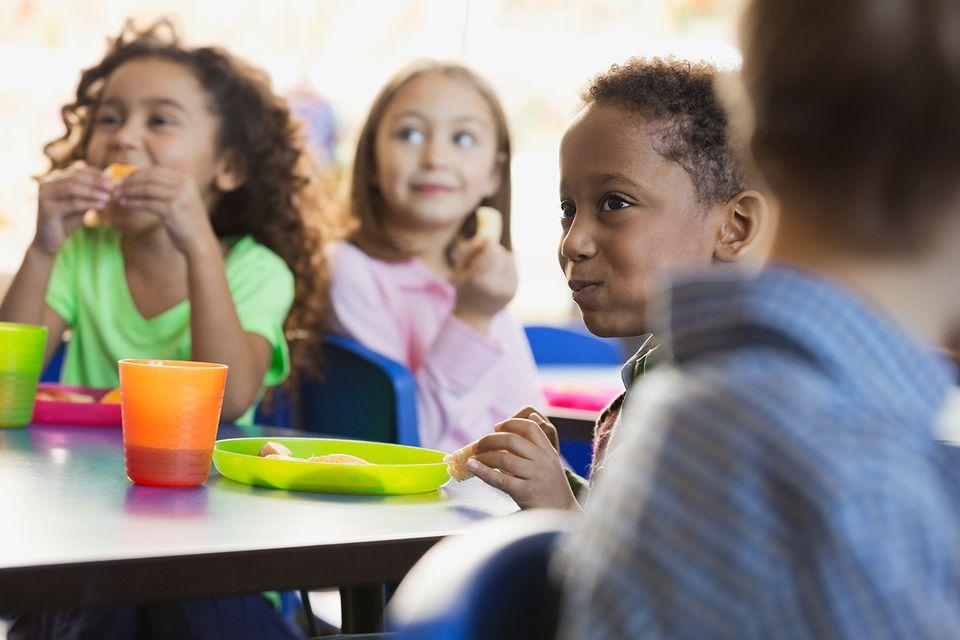 Children eating snacks in elementary school classroom.