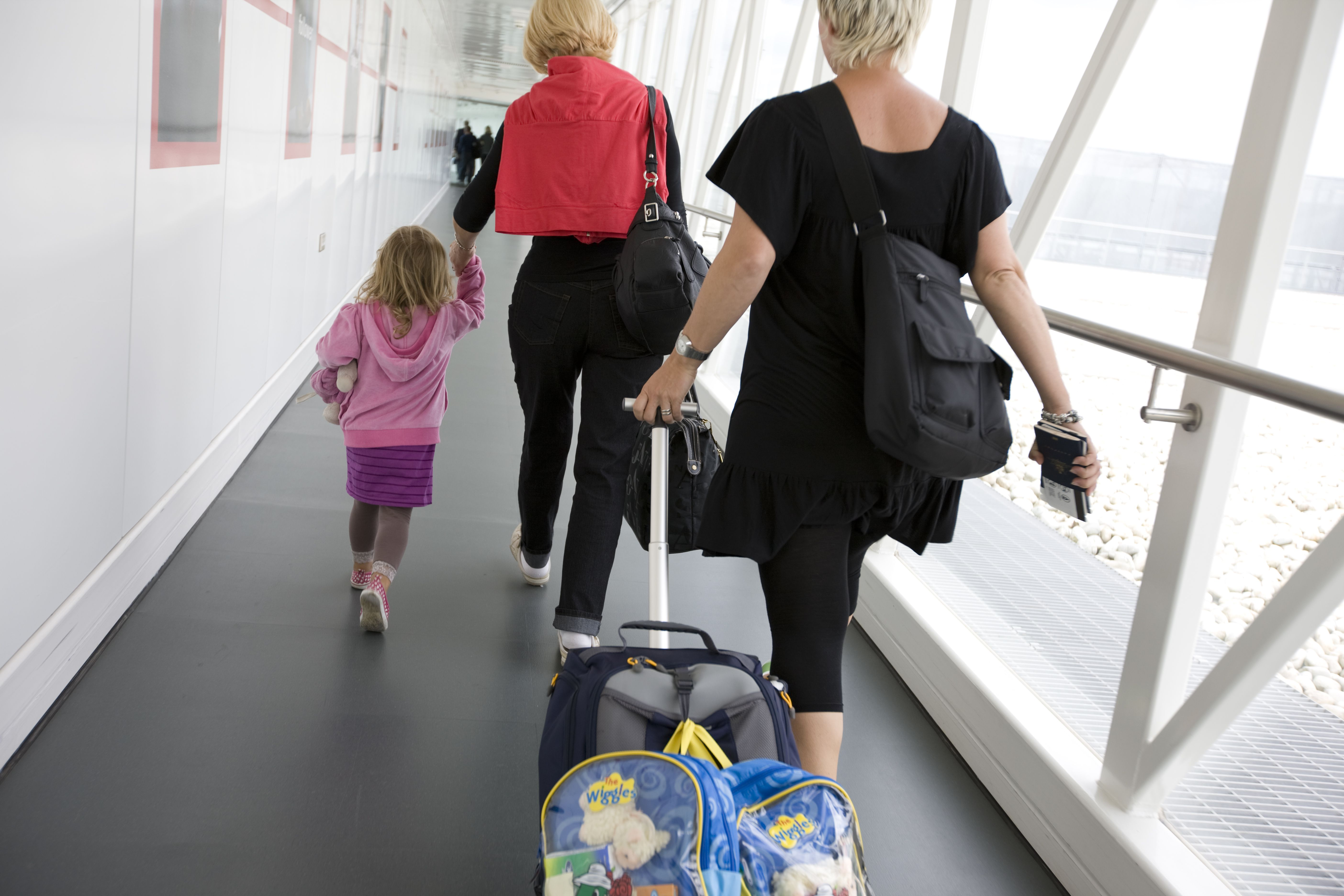 Two women and child walking along gangway to board airplane