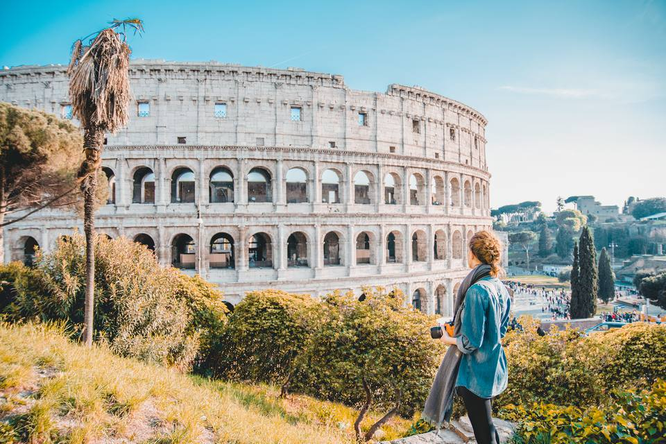 Woman standing in front of Roman colosseum