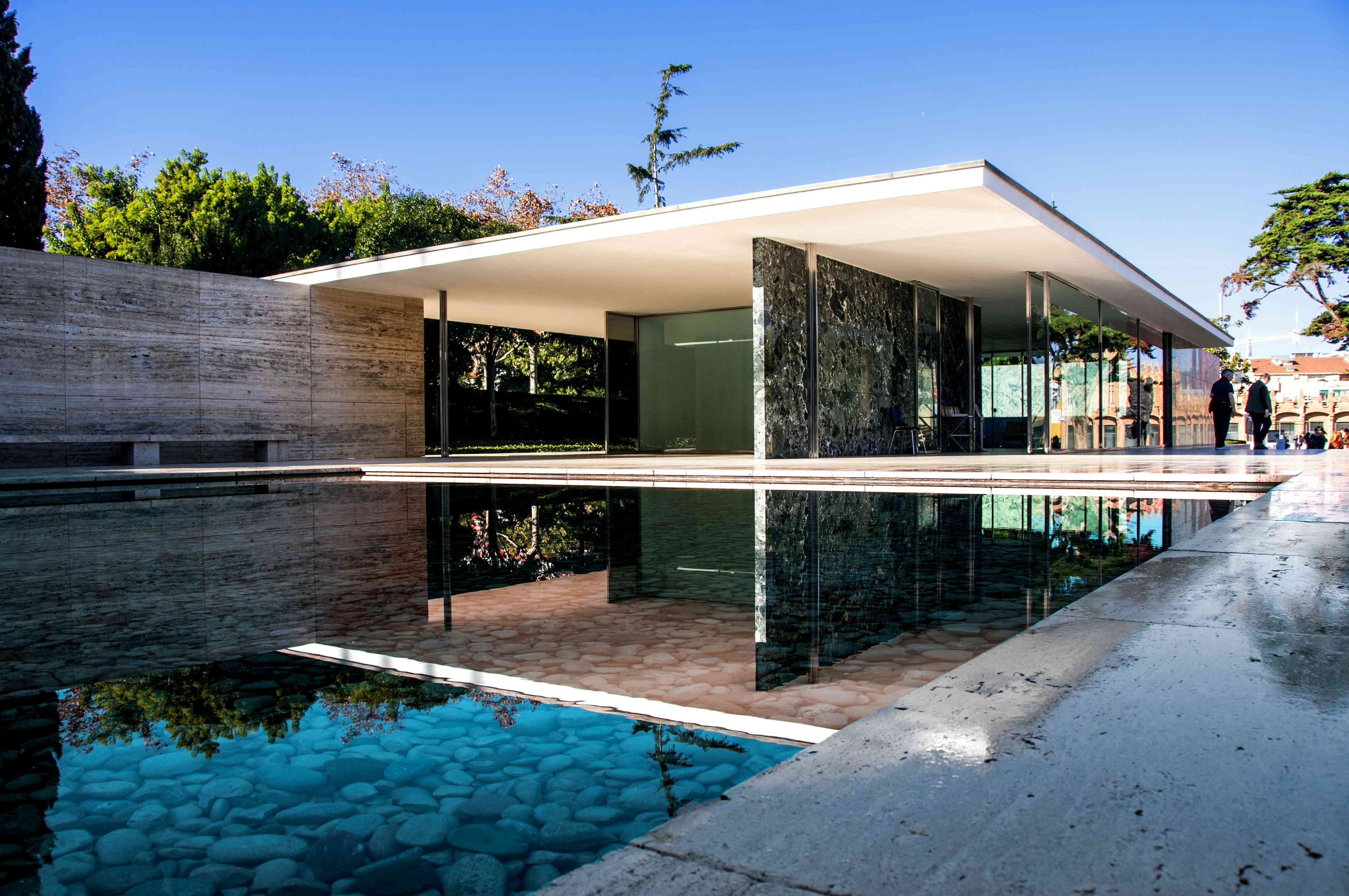 one story, flat-roofed minimalist building with a still pond