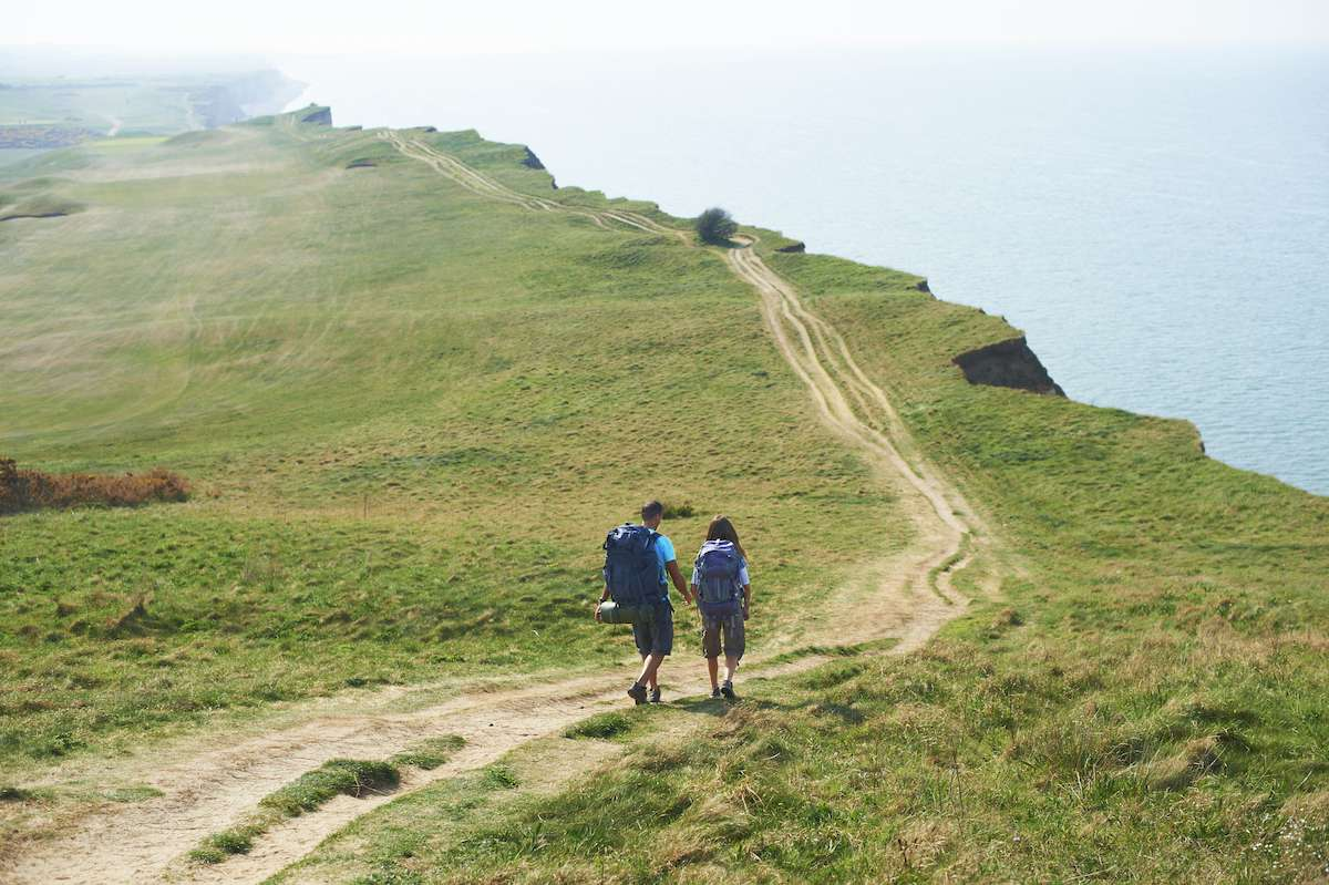 A man and woman hike along a coastal trail with backpacks strapped to their backs.