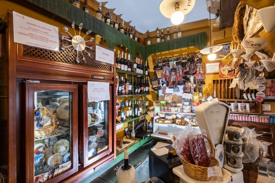 View of a cluttered restuarant with many bottles of wines, cheeses, and cured meats