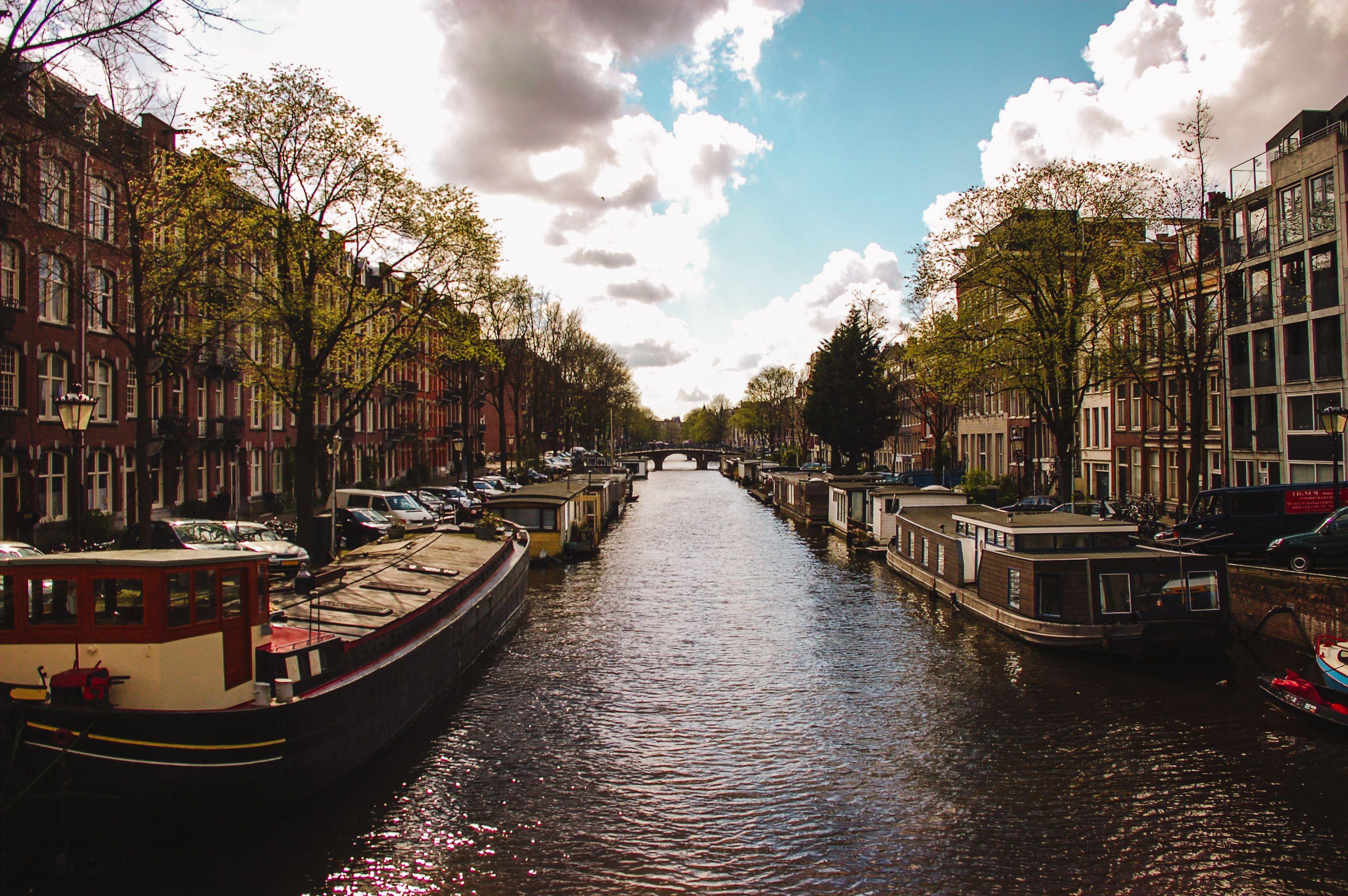 Un canal en Amsterdam bordeado de casas flotantes atracadas