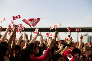 Group of people waving Canadian flags