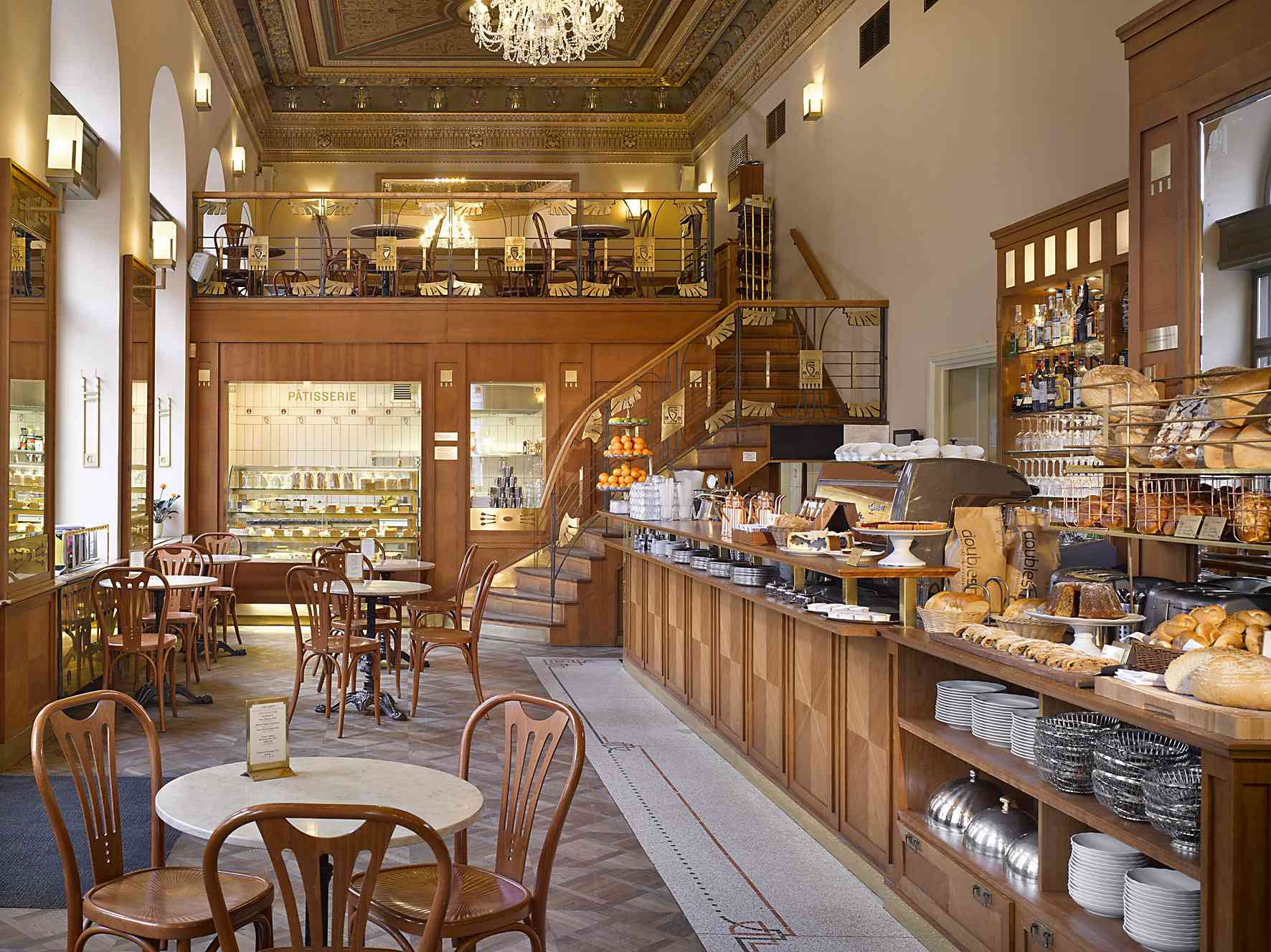 Warm wooden interior of Café savoy. The left side of the image has tables and chairs and the right side has a pastry case and the register. There are stairs in the back that lead to a lofted seating area