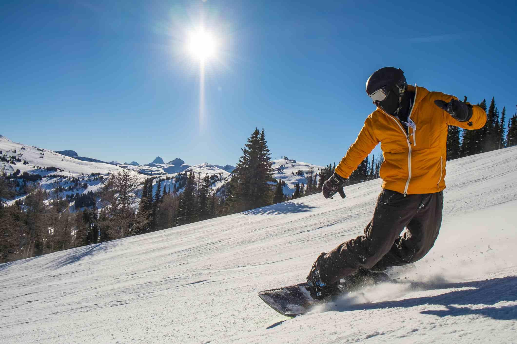 Snowboarder cranks turn on mountain slope