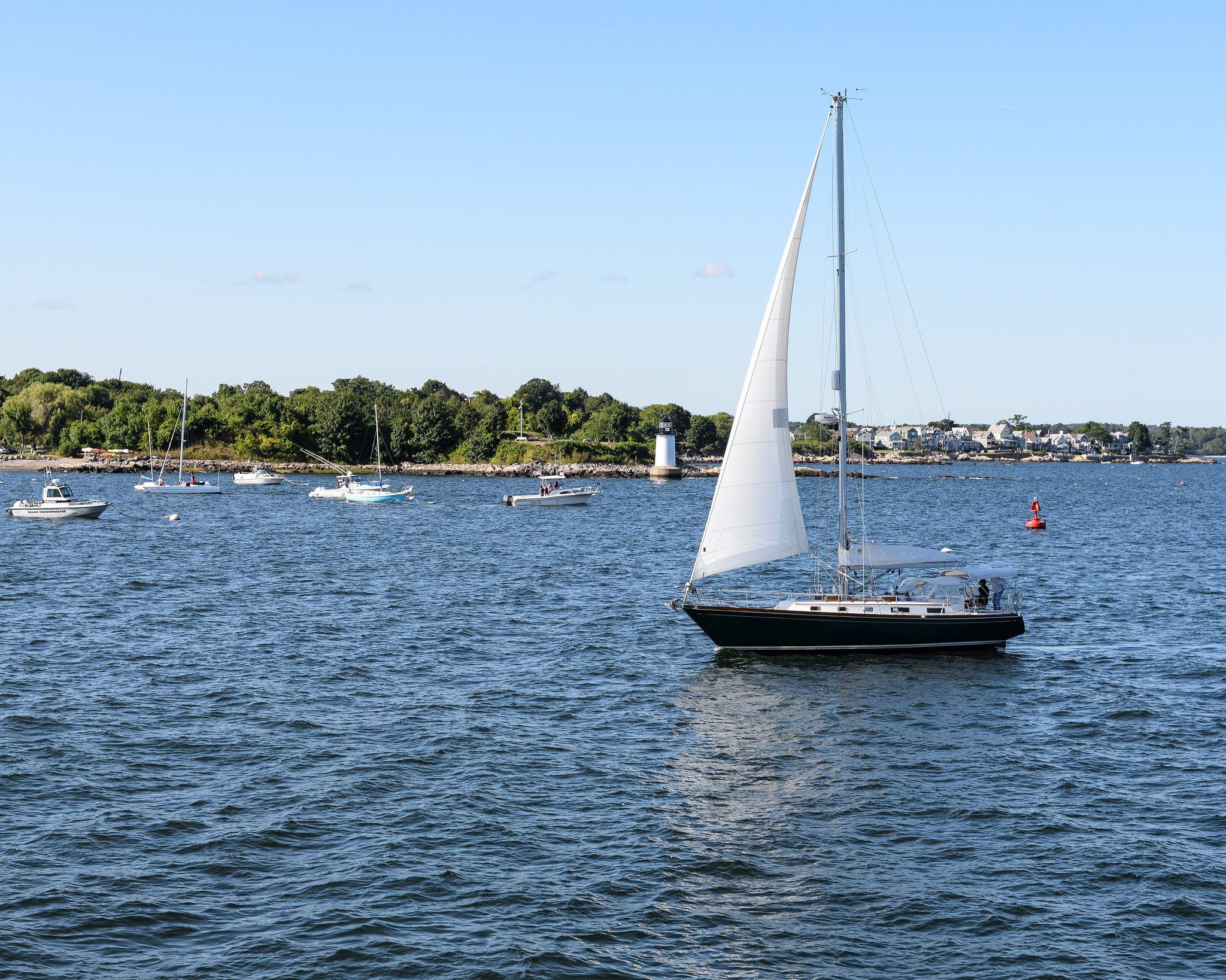 White sloop sailboat entering harbor