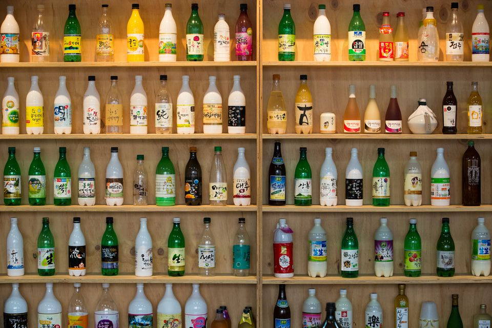 Bottles of makgeolli, Korean rice wine, on a wooden shelf