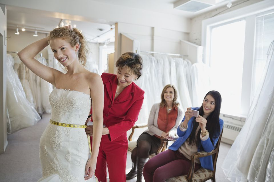 Woman in wedding dress at bridal store getting measured