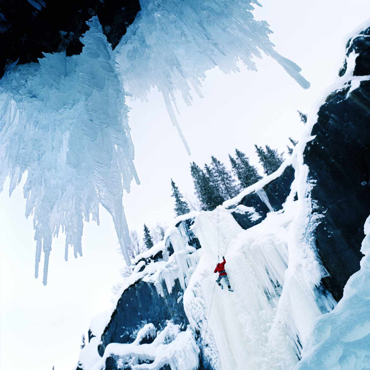 Ice climber on a frozen waterfall in Norway