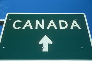 A green road sign indicates that Canada is just ahead