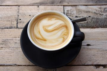 Flat white coffee in a black cup and saucer on a wooden cafe table