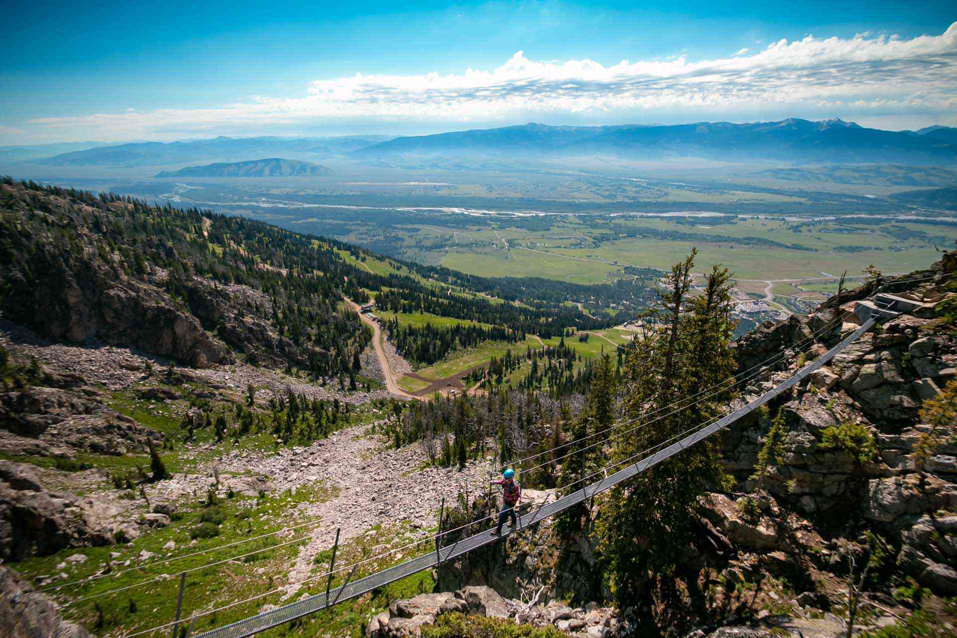 One person walking across a suspension bridge on Jackson Hole Mountain in summer
