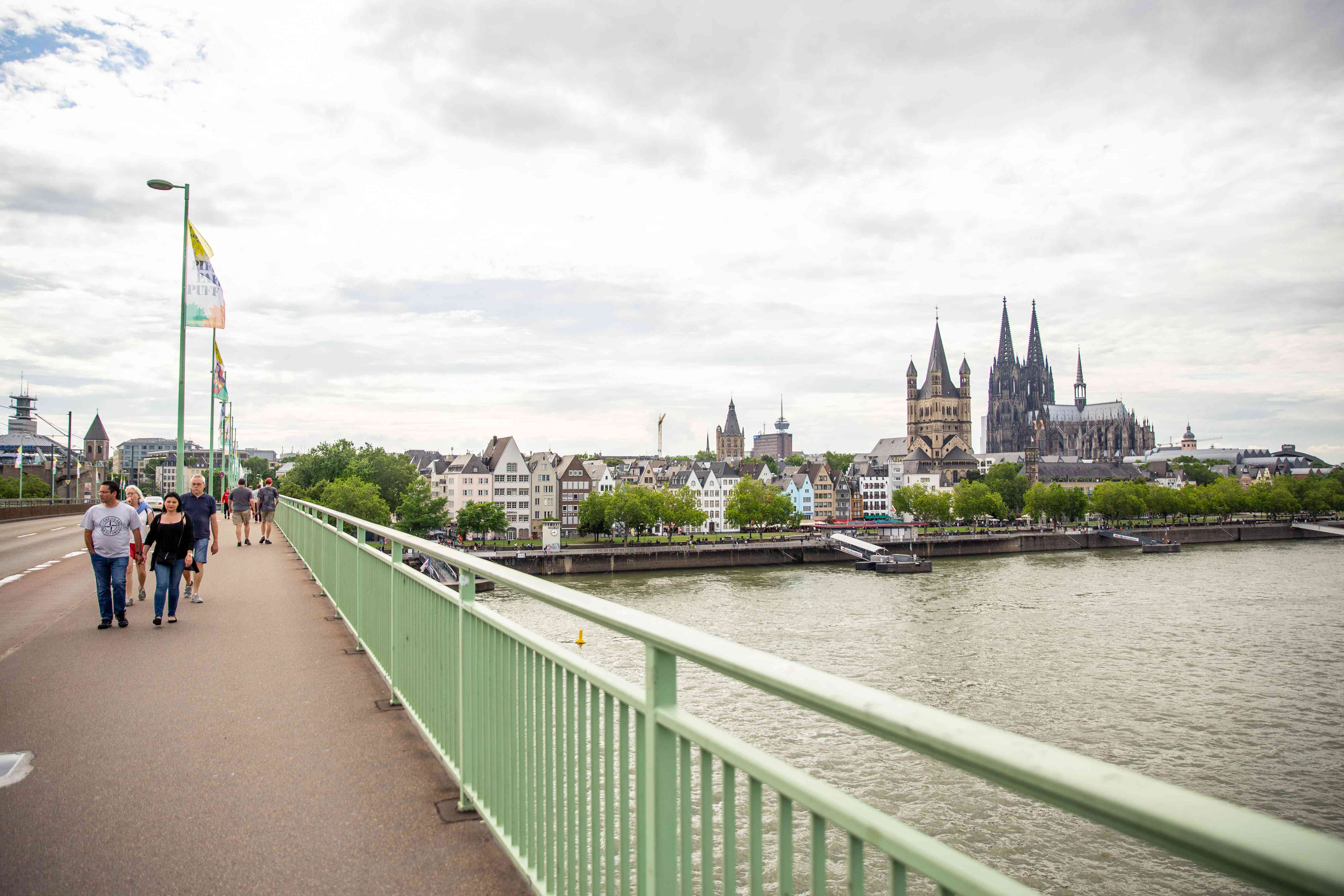 A shot of the view from the Deutzer bridge and people walking across it.