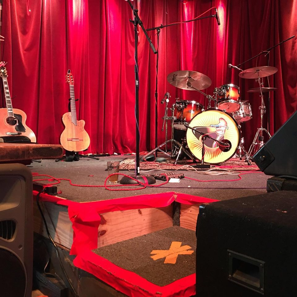 Drum set, speakers and electric and acoustic guitar on a small stage