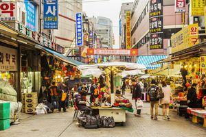 People walking past vendors in Namdaemun Market, Myeong-dong, Seoul
