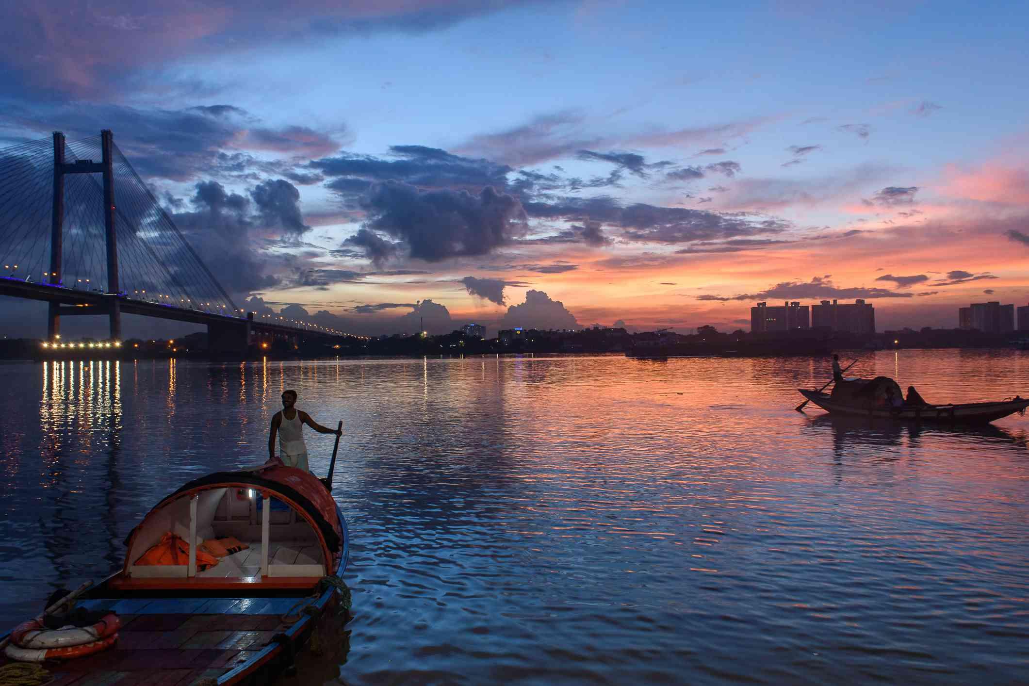 Silhouette of Vidyasagar Setu bridge at twilight with a wooden boat on Hoogly river.