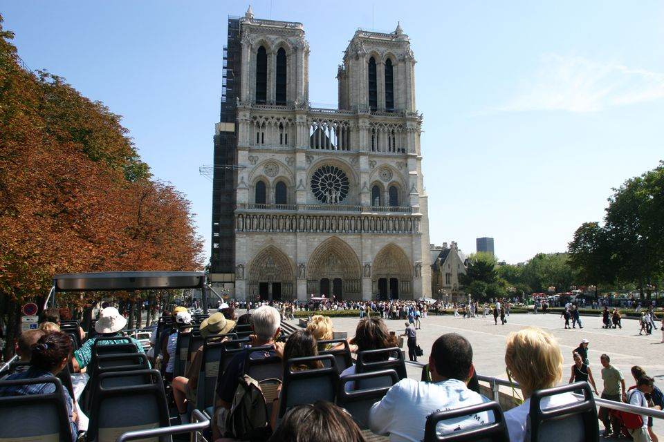 Tourists on a bus viewing Notre-Dame.
