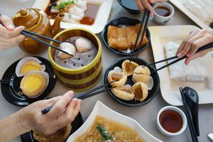 Group of friends eating dim sum meal with chopsticks