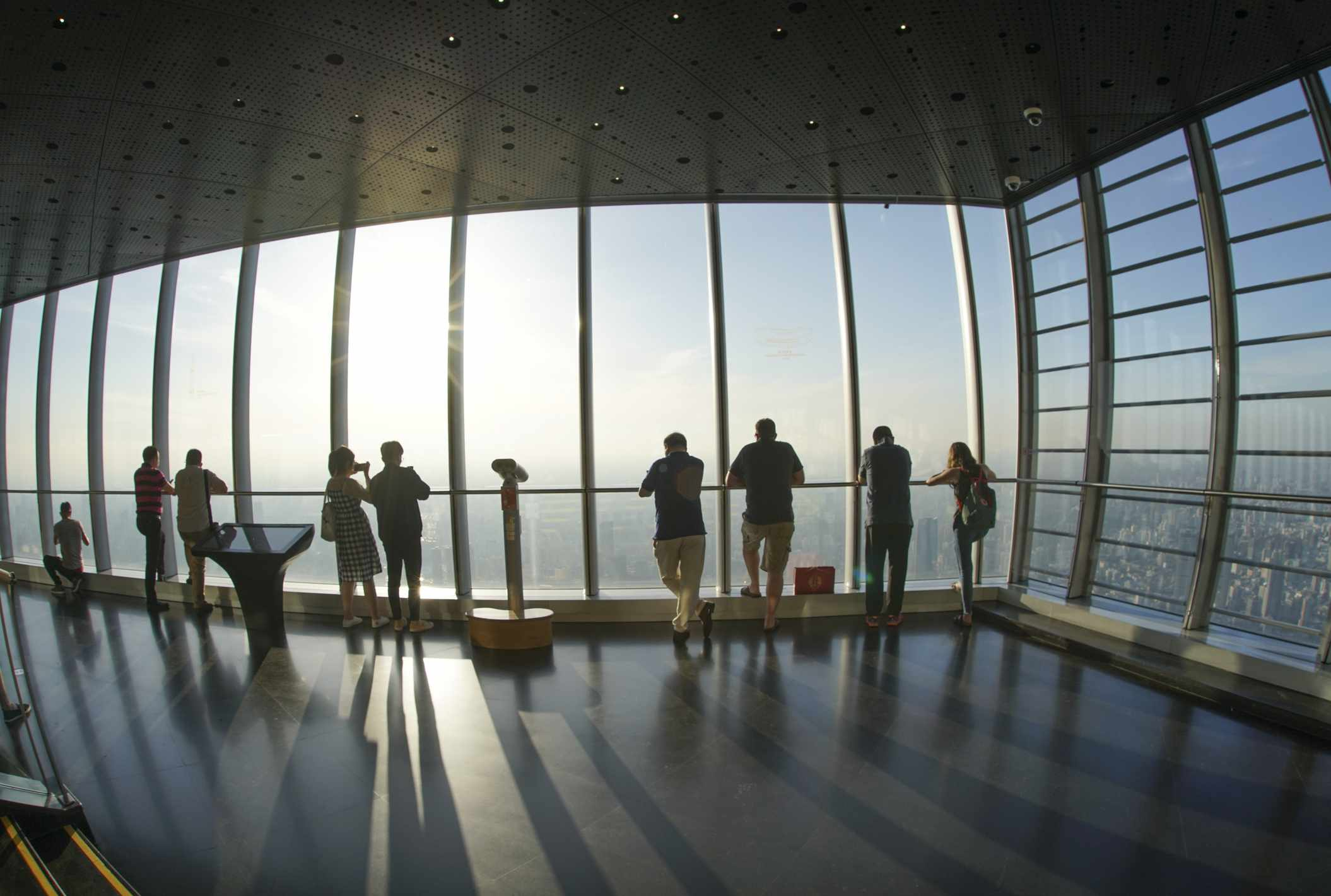 tourist standing at Shanghai tower top floor observation deck looking Puxi city